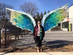 Art Works Now's Barbara Johnson in front of beautiful Angel Wings at Art Works Now. Photo courtesy of Barbara Johnson.