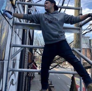 Freddy Castillo working on mural at Marathon Deli