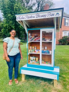 Yolanda Rivera Quintanilla standing by Lewisdale Blessings Box